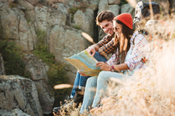 graphicstock-side-view-of-adventure-couple-with-map-sitting-on-slope-near-the-canyon_Bu_7wBL3x.jpg